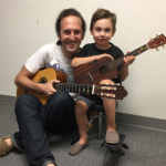 Image of a 4 year old kid and teacher posing at the end of their guitar lesson.