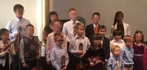 Kids posing together in a group photo after a guitar, flute, violin, and piano recital.