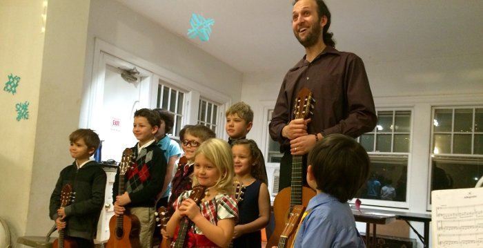 Image of 9 child guitar students and teacher posing at the end of the Spring Guitar Recital