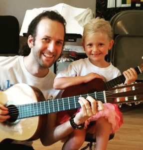 Image of teacher and 4 yr old kid posing at end of guitar lesson.