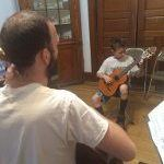 Image of student and teacher playing together during a guitar lesson. Student is an 8 yr old child.