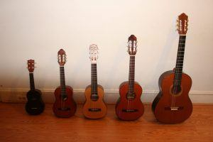 Image of rental guitars shown side-by-side. Sizes range from small-child to full-sized adult guitars.